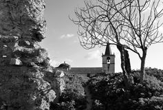 The old walls of the fortress with a leafless tree and an old church walls in black and white. Photo of the old and abandoned walls of the fortress with a stock photography