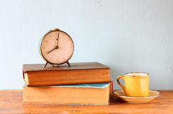 Photo of old alarm clock over wooden table, with faded retro effect Royalty Free Stock Photography