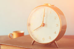 Photo of old alarm clock over wooden table, with faded retro effect Stock Image
