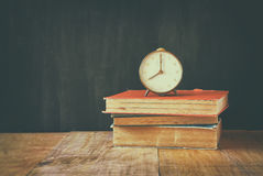 Photo of old alarm clock over wooden table, with faded retro effect Royalty Free Stock Photos