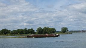 Photo of an old boat rusting away. A rusting old boat left to rust away with trees and and a town in the back ground Stock Photos