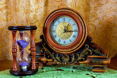 Photo of an old clock and sandglass on brown background Stock Images