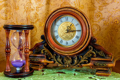 Photo of an old clock and sandglass on brown background Stock Photo