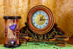 Photo of an old clock and sandglass on brown background Stock Photos