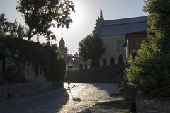 Photo of old cozy paving stone street in the sunny summer morning and backlight stock photography