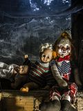 Scary dolls by the window. Photo of old dolls and an axe resting on an old window ledge covered in spiderwebs and dust Royalty Free Stock Images