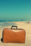 Photo in old image style. Old suitcase on the beach. Photo in old image style Stock Images