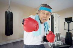 Old man punching camera in the fitness center Stock Photos