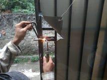 Old Man Welding a Corrosive Black Iron Handle of Gate. Photo Old Man Welding a Corrosive Black Iron Handle of Gate royalty free stock photos