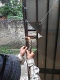 Old Man Welding a Corrosive Black Iron Handle of Gate. Photo Old Man Welding a Corrosive Black Iron Handle of Gate royalty free stock image