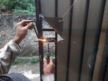 Old Man Welding a Corrosive Black Iron Handle of Gate. Photo Old Man Welding a Corrosive Black Iron Handle of Gate stock photos