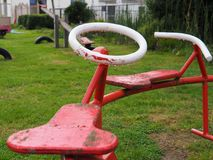 Old red and white spinning tool standing in the rain. Photo of an old red and white spinning tool from a playground in the rain Royalty Free Stock Image