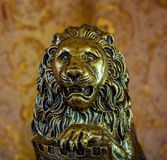 Old statuette of lion on brown background Stock Photos