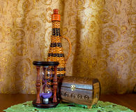 Photo of an old sandglass, bottle an casket on brown background Stock Photos
