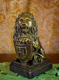 Photo of an old statuette of lion on brown background Stock Photography
