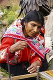 Old woman in Peruvian costume weaving alpaca sweater Royalty Free Stock Images