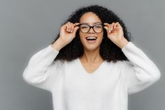 Photo of optimistic lovely woman looks happily through spectacles, keeps hands on rim of spectacles, notices something pleasant, stock photo