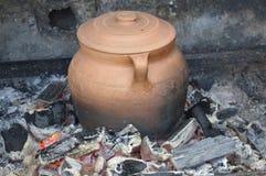 Jar made of clay on the floor. Photo of orange and black jar made of clay on the floor stock images