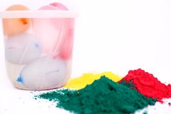 Photo of organic color with water balloons in bucket for holi festival. Isolated on the white background royalty free stock image