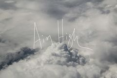 Aim High Motto Over The clouds. A photo over the clouds with a handwriting motto saying ``Aim High stock photo