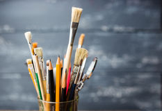Photo of paint brushes in a glass standing on old wooden table, Royalty Free Stock Photography
