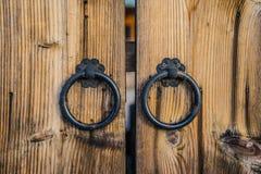 Pair of antique iron door handles on wooden door stock photo