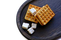 Viennese waffles and. Photo of a pair of typical viennese waffles and a few pieces of eastern pastilles served on wide neat dark plate made of dry oak wood royalty free stock image