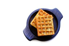 Viennese waffles on wooden plate. Photo of a pair of typical viennese waffles served on dark round wooden plate. Viennese wafers usually are square and looks royalty free stock image