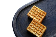 Viennese waffles on wooden board. Photo of a pair of typical viennese waffles served on large dark plate, made of dry oak wood. Viennese wafers usually are royalty free stock photo