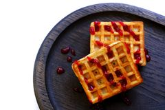 Viennese waffles on white. Photo of a pair of typical viennese waffles served on wide neat dark plate made of dry oak wood and poured on syrup. Viennese wafers stock photo
