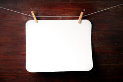Photo paper attach to rope with clothes pins. On wooden background Stock Images