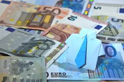 Photo with paper origami suit on euro banknotes Stock Images
