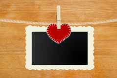 Photo paper and red heart hanging on rope on wooden background Stock Image