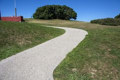 Sky and track 1. Photo of a park detail with green grass, blue sky and sunlight Stock Photo