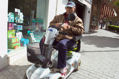 Man in an invalid scooter Royalty Free Stock Photography