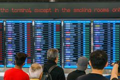 Passengers are looking for airline check-in counter on the screen royalty free stock photography