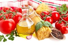 Photo of pasta with tomatoes,basil,oil,garlic at the top on white Stock Image
