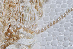Photo of pearl string and threads on white textile textured background Stock Image
