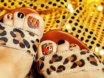 Photo of pedicure like butterfly design on gold background close up, mani pedi creative concept Royalty Free Stock Image