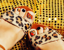 Photo of pedicure like butterfly design on gold background close up, mani pedi creative concept Royalty Free Stock Photos