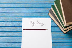 photo of pencil, books and paper with My Story words near gumshoes on blue wooden table stock image