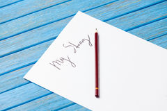 Photo of pencil and paper with My Story words near gumshoes on b Royalty Free Stock Images