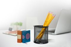 Photo of pencils in plastic glass, some pens. And papers on the table in office royalty free stock photos