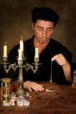 Photo pendulum. Fortune-teller holding a pendulum above a wedding photo (this photo is model released stock photos