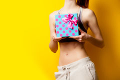 Photo of perfect slim female body with cute gift in the hands on. The wonderful yellow background Royalty Free Stock Photo
