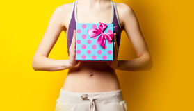Photo of perfect slim female body with cute gift in the hands on. The wonderful yellow background Stock Image