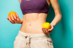 Photo of perfect slim female body with orange and apple in the h. Ands on the wonderful blue background Royalty Free Stock Photography