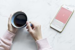 Photo of Person Holding Blue Cup Near Smartphone Royalty Free Stock Photos