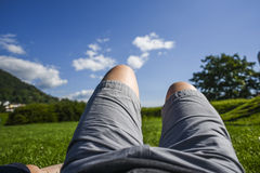 A photo of a person`s legs lying on the grass on a forest backgr. Ound, resting and relaxing while on a sunny summer day Royalty Free Stock Photo