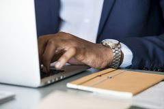 Photo of Person Wearing Gray Analog Watch Tapping Keyboard of Laptop Stock Image